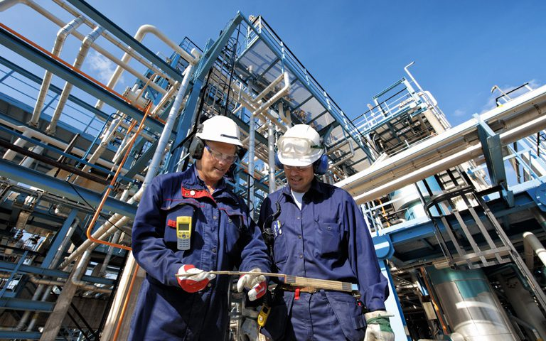 Two Oil and Gas Workers in front of Combined Cycle Plant piping