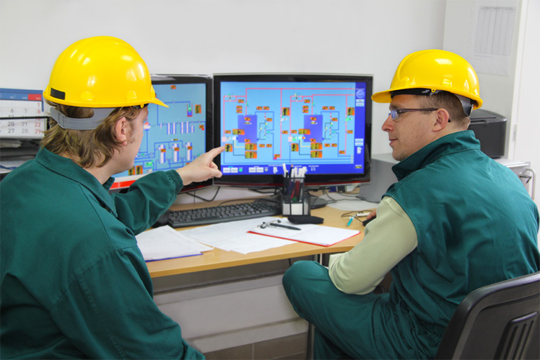Workers in control room engaged in power plant operator training