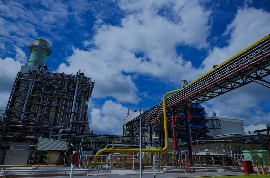 Combined Cycle Plant with red and yellow piping and blue sky