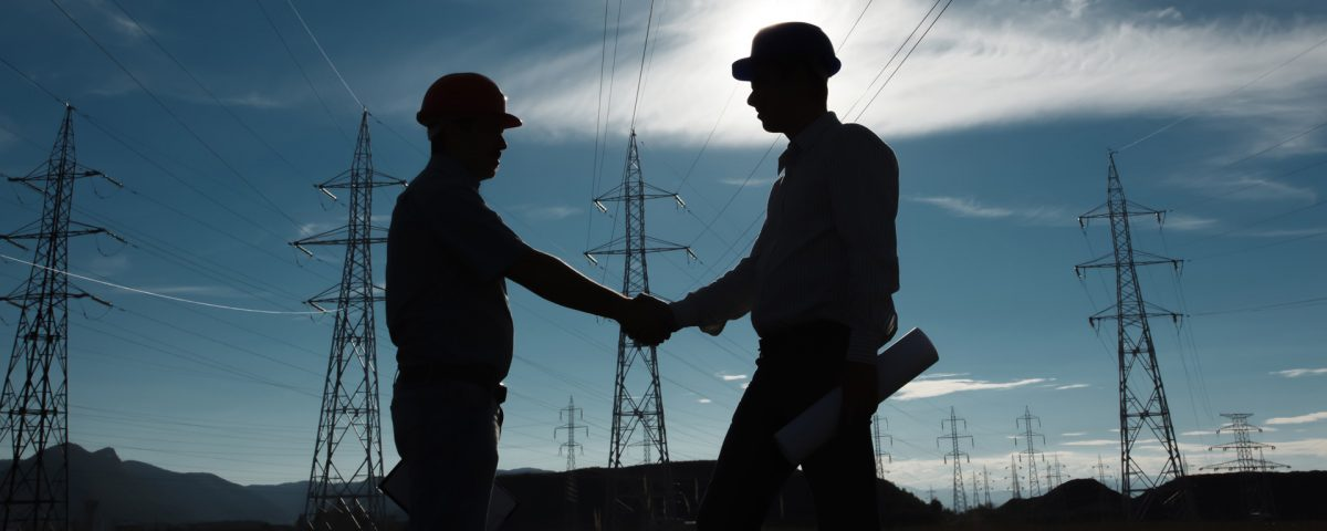 Silhouette of Engineers Shaking Hands in front of High Voltage Power Lines
