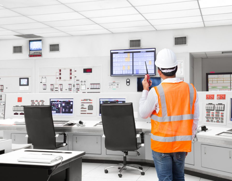 Engineer wearing hard hat and safety vest, using radio to communicate with power plant operators.